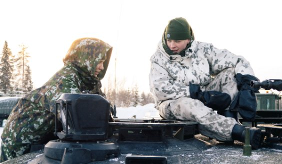 Two conscripts on top of a tank on a sunny winter day. The conscript on the left is wearing a cold weather jacket, model m05. The one on the right is wearing a snow camouflage suit.