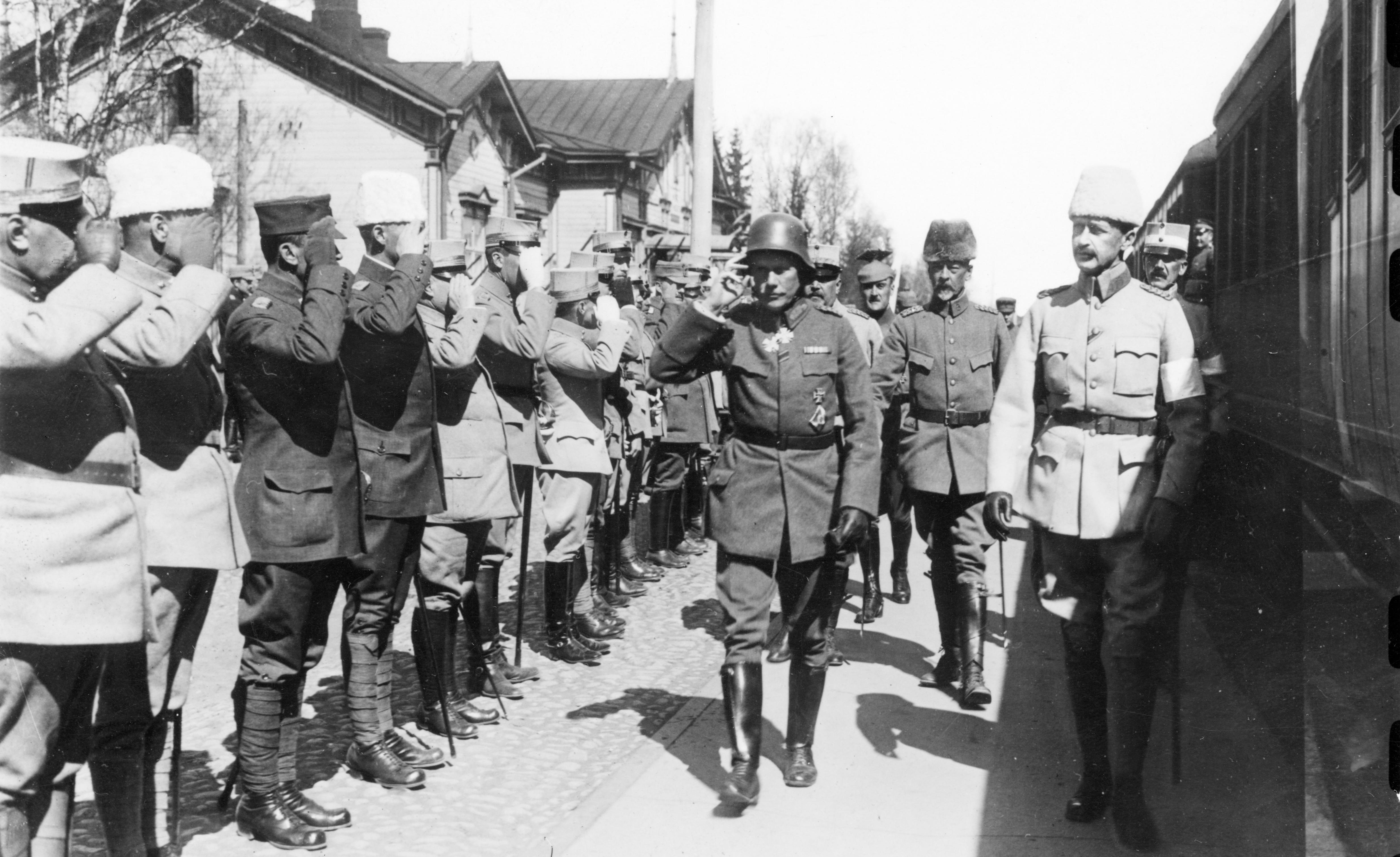 Sotilaat rivissä tervehtivät ohi marssivia upseereita, mustavalkokuva